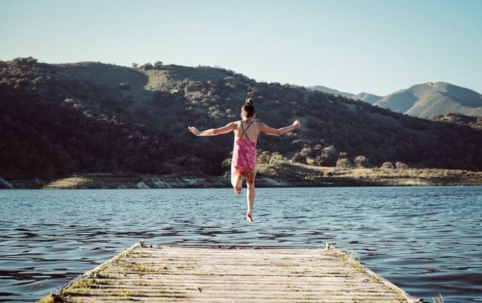 Girl leaping off a jetty into water