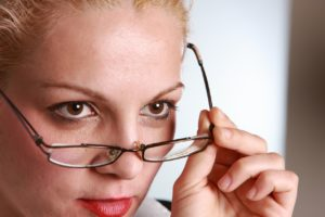 Woman looking over her glasses looking showing assertiveness